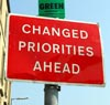 red street sign reads 'Changed Priorities Ahead'